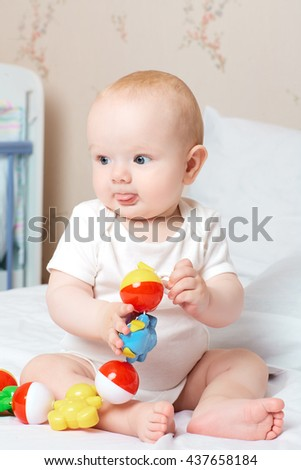 Calm baby boy with tongue holds the toy. - stock photo