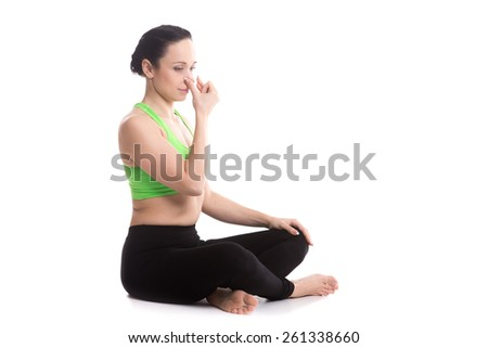 Calm beautiful girl practicing hatha yoga nadi shodhana pranayama (Alternate Nostril Breathing), sitting cross-legged in Easy Pose, Sukhasana, meditation, Vishnu mudra, copy space - stock photo
