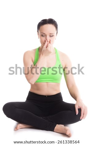 Calm beautiful girl practicing hatha yoga nadi sodhan pranayama (Alternate Nostril Breathing), sitting cross-legged in Pleasant Pose, Sukhasana, meditation, Vishnu mudra - stock photo