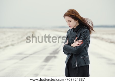 calm beautiful young girl freezes in winter on the road