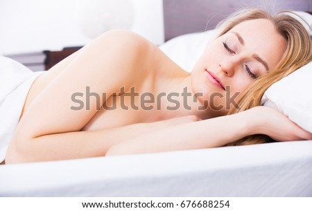 Calm blonde woman without pyjamas having a nap in the bed with hands beside her head