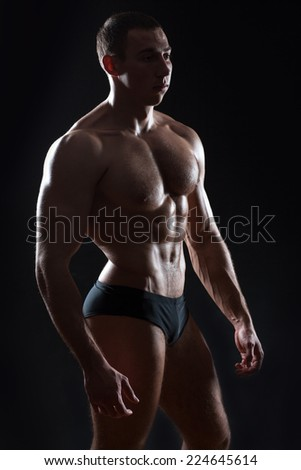 Calm bodybuilder standing on a dark background it shine large muscles of the body.