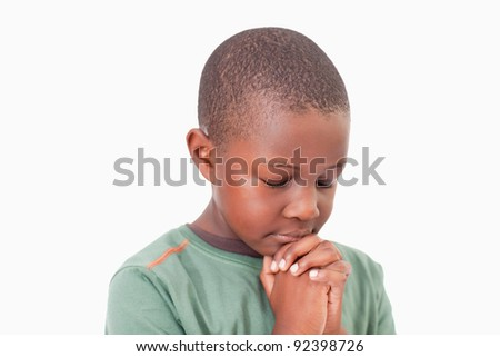 Calm boy praying against a white background - stock photo
