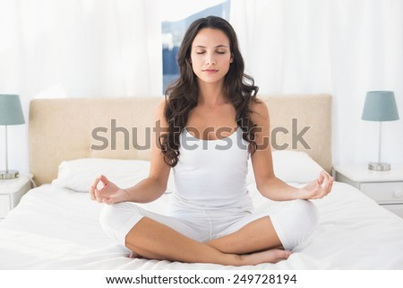 Calm brunette doing yoga on bed at home in bedroom - stock photo