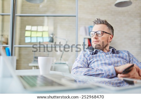 Calm businessman in eyeglasses sitting in office - stock photo
