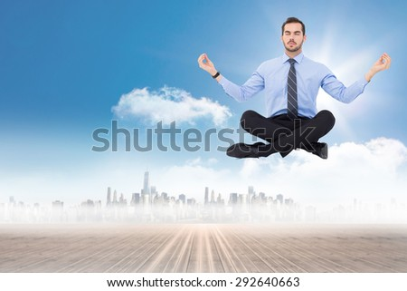 Calm businessman sitting in lotus pose against cityscape on the horizon
