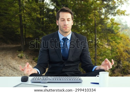 Calm businessman sitting in lotus pose against tarmac curved country road in forest - stock photo