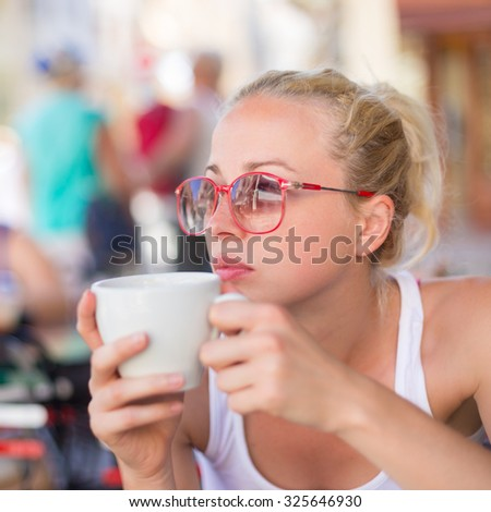 Calm casual blond lady enjoying cup of coffee outdoor in typical italian  street coffee house on warm summer day. - stock photo