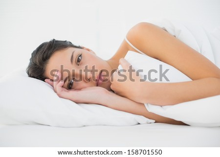 Calm casual brunette lying in her bed in bright bedroom - stock photo