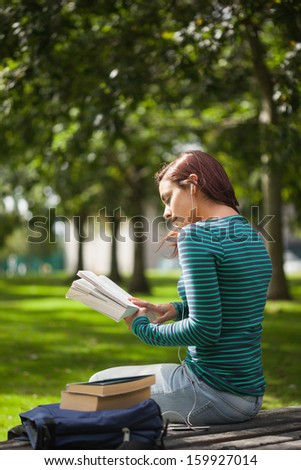 Calm casual student sitting on bench reading on campus at college - stock photo