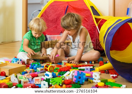 Calm children playing with toys in home interior - stock photo