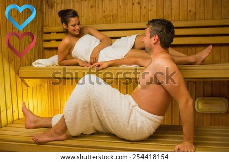 Calm couple relaxing in a sauna and chatting against hearts - stock photo