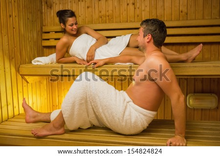 Calm couple relaxing in a sauna and chatting wearing white towels - stock photo