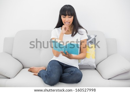 Calm dark haired woman reading a book sitting on couch in bright living room - stock photo