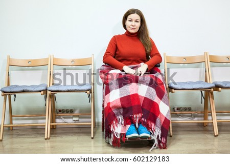 Calm disabled woman in wheel-chair with blanket on legs looks at camera while sitting in room