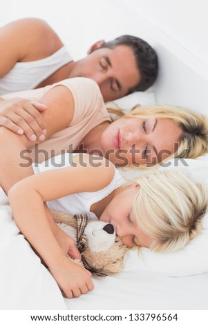 Calm family sleeping together on a same bed - stock photo