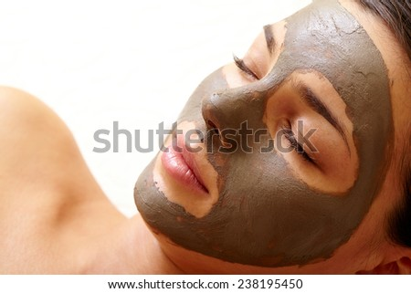 Calm girl with clay mask on her face - stock photo