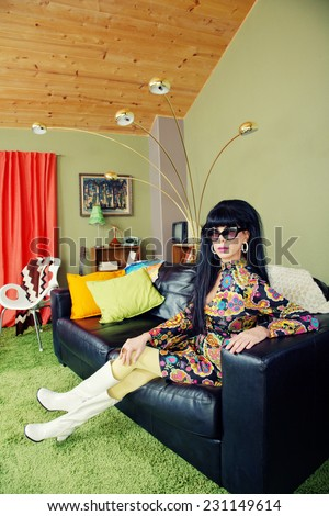 Calm groovy woman sitting on leather sofa - stock photo