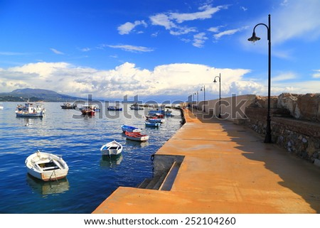 Calm harbor with small fishing boats protected by the pier in the morning, Koroni, Greece - stock photo