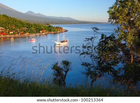 Calm lagoon with sail boat and buildings in forest on a hill side - stock photo