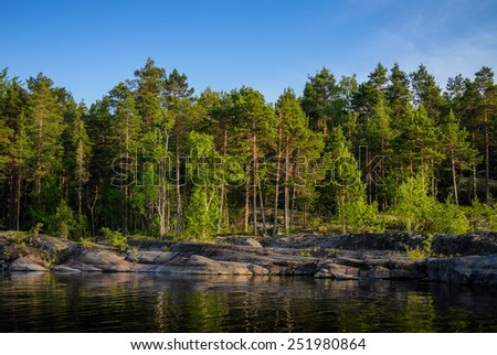 calm lake in stone shores with forest over it - stock photo