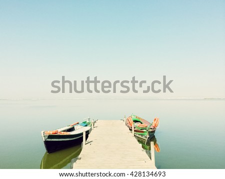 Calm lake with two fishing boats. Fresh water lagoon in Albufera de Valencia, Spain.