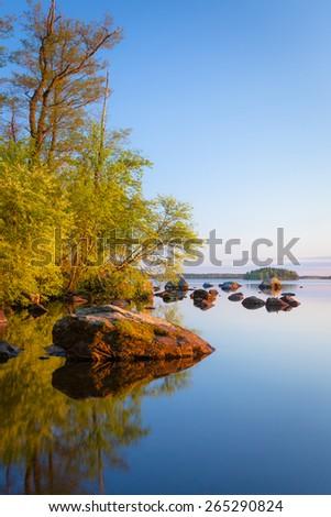Calm lakeside at sunset - stock photo