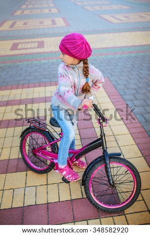 Calm little girl riding bicycle in city park. - stock photo