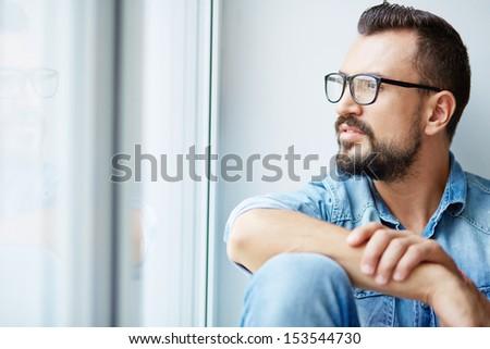 Calm man in denim shirt and eyeglasses looking through window - stock photo