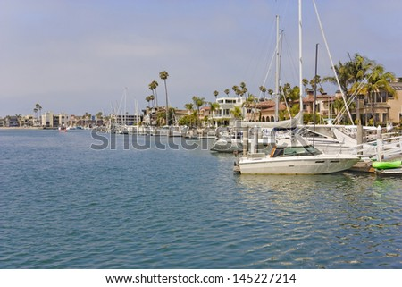 Calm marina in suburban Southern California. Waterfront scene of boats anchored at Naples pier, Long Beach. Horizontal, palm trees, residential buildings in background. Blue hazy sky, clouds. - stock photo