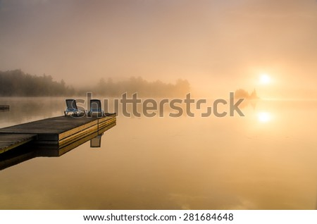 Calm misty morning by the lake in Algonquin Park - stock photo