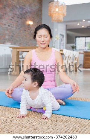 Calm mother meditating on mat at home while baby daughter is looking around - stock photo
