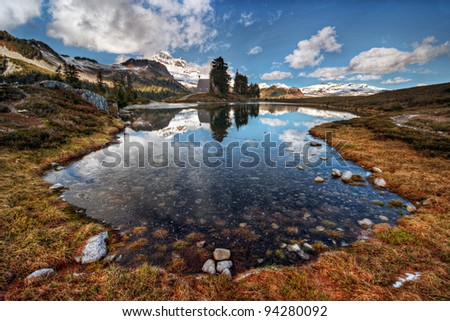 Calm mountain lake with distant hut on the shore - stock photo