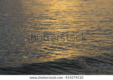 Calm ocean water reflecting summer sunset light while wave crashes on beach coast. - stock photo