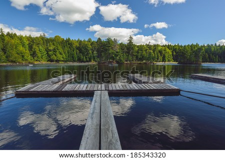 Calm peaceful cove on a freshwater lake with puffy white clouds reflected as a wooden ramp extends out into the water for a small boat dock - stock photo