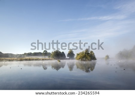 Calm peaceful lake with mist hanging over water on frosty Autumn Fall morning landscape - stock photo