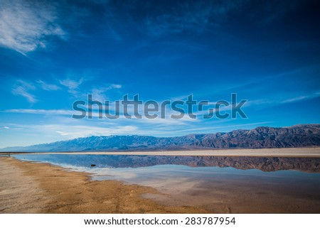 Calm placid water sits in the dry lake bed of Death Valley National Park. - stock photo