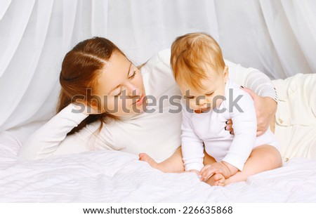 Calm portrait mother and baby on the bed home