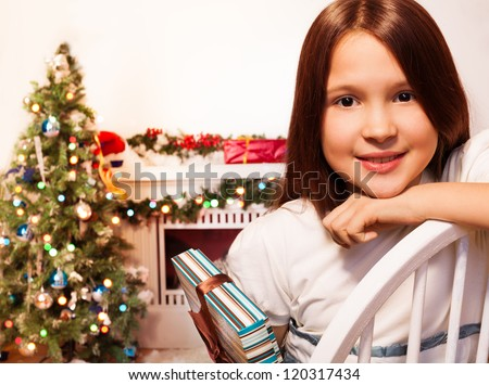 Calm positive girl sitting with present with new year tree on background