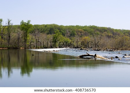 Calm river. Mirror reflection. Waterfall edge. Tree trunk floating. Fast current. Spring time. Nature background. Great falls national park. Virginia. USA April 2016 - stock photo