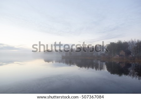 Calm scenery. Barns and forest are reflecting from the water. Foggy landscape.