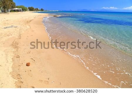 Calm sea and golden sand on a Greek beach  - stock photo