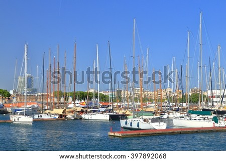 Calm sea and sail boats by the pier inside the harbor of Barcelona, Catalonia, Spain - stock photo