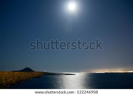 calm sea at night with moon illuminating - stock photo