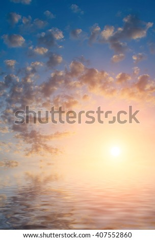 Calm sea, golden clouds and the last rays of the sun. Natural seascape