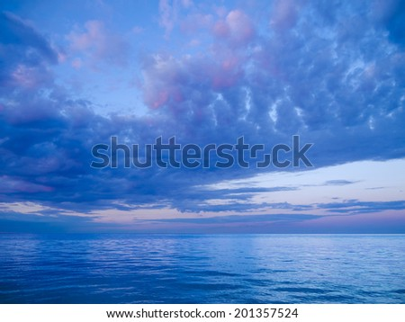 calm sea with beautiful moody and cloudy evening sky - stock photo