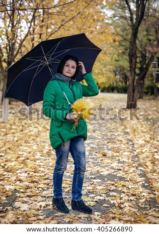 Calm single woman standing under umbrella on sidewalk covered with leaves along path of maple trees in autumn theme portrait - stock photo