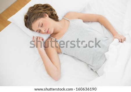 Calm slender woman lying sleeping on her bed under the cover in her bedroom