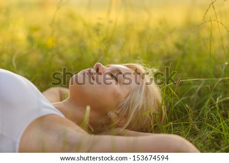 calm smiling woman closed eyes and resting in the park - stock photo
