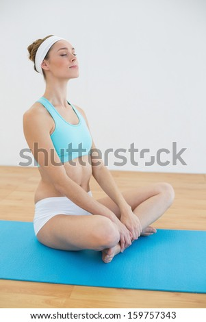 Calm sporty woman sitting on blue exercise mat meditating with eyes closed